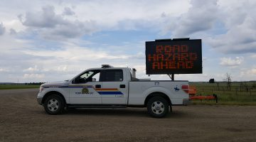 PHOTO - RCMP Vehicle in front of Caution Sign on Highway 21