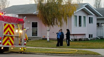 Family members gather outside their home while firefighters pack up after handling a house fire at the residence. Photo by James Wood/106.1 The Goat/Vista Radio